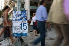 <p>Affiche électorale dans une rue d'Athènes. Les banques grecques ont enregistré une forte hausse des sorties d'argent à l'approche du scrutin législatif de dimanche prochain. De nombreux Grecs craignent que le résultat des élections ne pousse leur pays hors de la zone euro. /Photo prise le 13 juin 2012/REUTERS/Pascal Rossignol</p>
