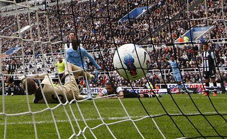 Manchester City's Yaya Toure scores his second goal as Newcastle United's Jonas Gutierrez tries to block his shot during their English Premier League soccer match in Newcastle, north east England May 6, 2012. REUTERS/David Moir