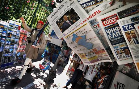 A presidential guard marches by a newspaper stand featuring news about Greece's election results in Athens June 18, 2012. REUTERS/Pascal Rossignol