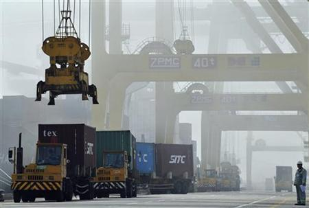 Shipping containers are loaded onto trucks at Dayaowan port of Dalian, Liaoning province June 10, 2012. REUTERS/Stringer