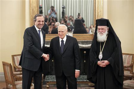 Newly appointed Greek Prime Minister Antonis Samaras (L) shakes hands with President Karolos Papoulias (C) as Greece's Orthodox Archbishop Ieronymos looks on after a swearing in ceremony at the Presidential palace in Athens June 20, 2012. Samaras pledged to pull his debt-stricken country back from the brink of bankruptcy on Wednesday in his first comments after being sworn in. REUTERS/Yorgos Karahalis