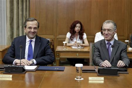 Newly appointed Greek Prime Minister Antonis Samaras (L) looks at his next Finance Minister Vassilis Rapanos during a cabinet meeting at the parliament in Athens in this June 21, 2012 file photo. Samaras, who underwent eye surgery on June 23, 2012, will not attend a summit of EU leaders on June 28-29, when Athens will seek to ease the punishing terms of its international bailout, a government spokesman said on June 24, 2012. Rapanos will also miss the summit having been rushed to hospital on June 22, 2012 before he could be sworn in, complaining of nausea, intense abdominal pains and dizziness. He remains in hospital. REUTERS/Yorgos Karahalis/Files