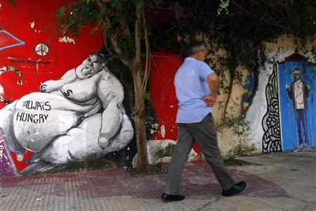 A man walks in front of a wall covered in graffiti in central Athens June 25, 2012. REUTERS/Pascal Rossignol