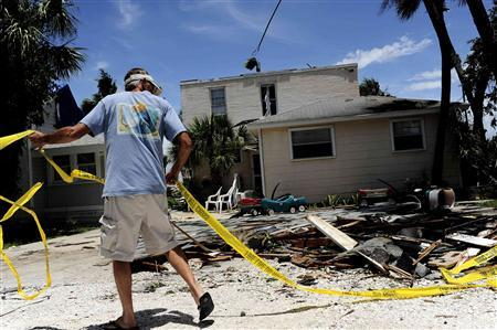 Mike Foster uses some spare fire line tape to rope off what remains of the roof that blew off his employer's property during the night on Pass-A-Grille Beach as high winds and storm surge associated with Tropical Storm Debby continue to affect the area in Florida, June 25, 2012. REUTERS/Brian Blanco