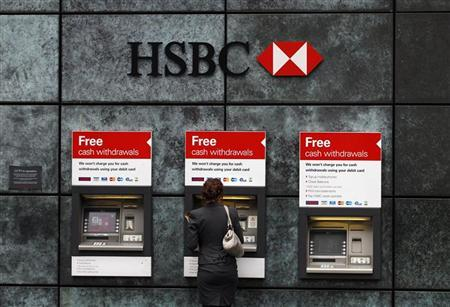 A woman uses a cash point machine at a HSBC bank in the City of London February 28, 2011.