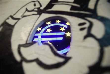A sculpture showing the Euro currency sign is seen through a photo board installed by Occupy protestors in front of the European Central Bank (ECB) headquarters in Frankfurt June 29, 2012. REUTERS/Alex Domanski
