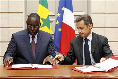 France's President Nicolas Sarkozy (R) and Senegal's President Macky Sall sign a partnership agreement at the Elysee Palace in Paris April 18, 2012. REUTERS/Benoit Tessier