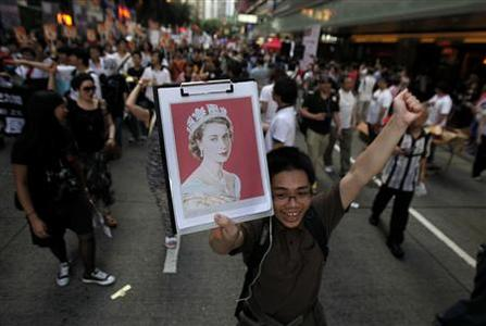 A pro-democracy demonstrator holds a portrait of Queen Elizabeth as he marches along downtown Hong Kong July 1, 2012, during the 15th anniversary of the territory's handover to China. REUTERS/Carlos Barria