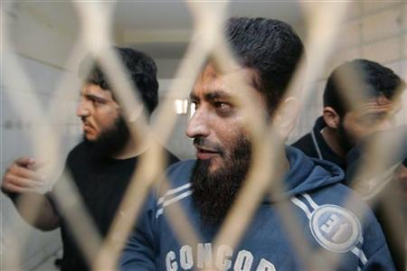 Defendants Tawfiq Saad al-Faqih, Nabil Ahmed al-Suraihi and Ismael Ali Ghurab stand behind bars at a state security court in Sanaa May 4, 2009. REUTERS/Khaled Abdullah