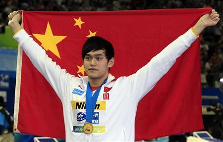 China's Sun Yang poses with his gold medal and national flag after the men's 1500m freestyle final at the 14th FINA World Championships in Shanghai July 31, 2011. REUTERS/Bobby Yip
