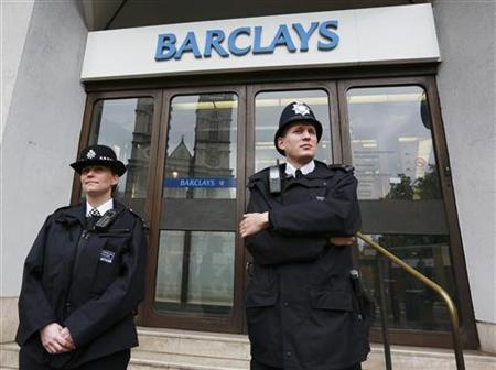 Police wait for protestors to appear at a branch of Barclays Bank in Westminster, central London, July 4, 2012. REUTERS/Olivia Harris