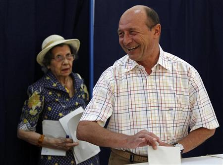 Romania's President Traian Basescu prepares to vote in Bucharest June 10, 2012. REUTERS/Bogdan Cristel