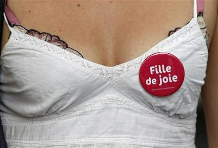 A prostitute wears a badge as she attends a demonstration with sex workers activists against a proposition to abolish prostitution in Paris July 7, 2012. The French Minister for women's rights wanted to eradicate the sex trade in France and new measures to stamp out prostitution. The badge reads, ''Girl of pleasure''. REUTERS/Regis Duvignau