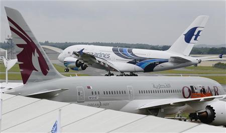 An Airbus A380, owned by Malaysia Airlines, lands behind a Boeing 787, owned by Qatar Airways, ahead of the Farnborough Airshow 2012 in southern England July 8, 2012. REUTERS/Luke MacGregor