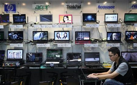 A shop attendant sits in front of a wall of laptops at a computer mall in Taipei August 31, 2011. REUTERS/Pichi Chuang