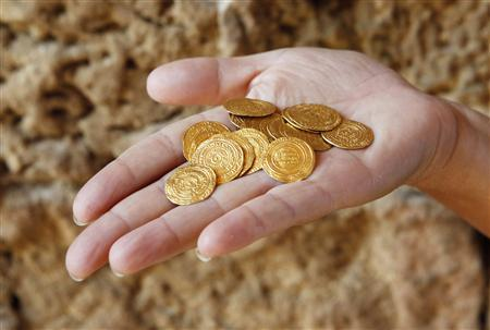 An Israel Nature and Parks Authority employee displays gold coins found hidden in a ceramic jug at the Arsuf cliff-top coastal ruins, 15 km (9 miles) from Tel Aviv, in this file pictur taken July 9, 2012. REUTERS/Baz Ratner/Files