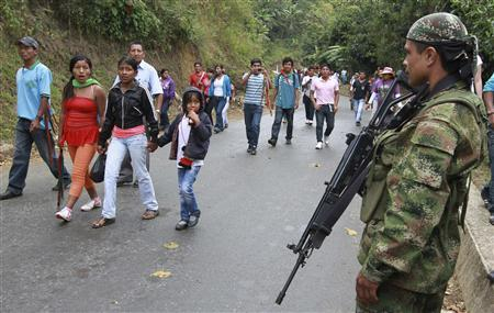A member of the Revolutionary Armed Forces of Colombia (FARC) watches a group of indigenous people as they walk by an illegal check point at one of Toribio's main access road, in the province of Cauca, July 11, 2012. REUTERS/Jaime Saldarriaga