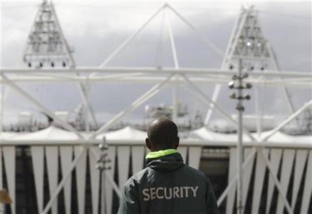 A security guard walks towards the Olympic Stadium in the London 2012 Olympic Park at Stratford in London July 13, 2012. REUTERS/Luke MacGregor