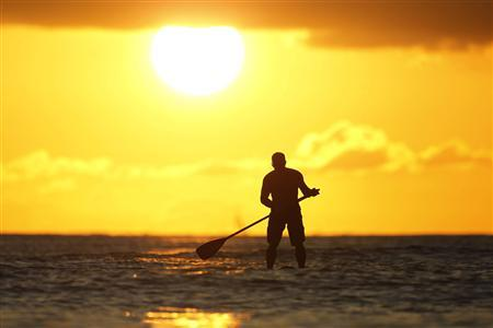 A paddle board rider surfs at sunset on New Year's Eve at Waikiki Beach in Honolulu, Hawaii, in this December 31, 2011 file photo. REUTERS/Jason Reed/Files