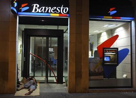 A man sleeps outside a Banesto bank branch in central Barcelona June 27, 2012. REUTERS/Andrea Comas
