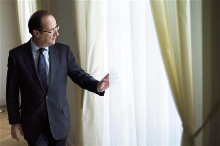 France's President Francois Hollande looks through the window of the previous apartment of former Interior Minister Claude Gueant as he visits the Alma site, a department of the Elysee Palace in Paris July 19, 2012. REUTERS/Fred Dufour/Pool
