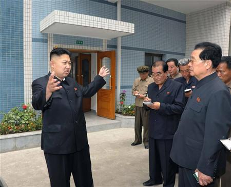 North Korean leader Kim Jong-Un (L) visits a newly built apartment house in Changjon Street area in this undated picture released by the North's official KCNA news agency in Pyongyang May 31, 2012. REUTERS/KCNA