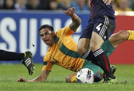 Australia's Tim Cahill is fouled by Japan's Keisuke Honda during their 2014 World Cup qualifying soccer match in Brisbane June 12, 2012. REUTERS/Daniel Munoz