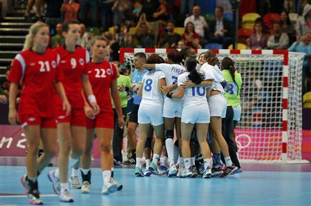 France's players (R) celebrate after defeating Norway in their women's handball Preliminaries Group B match at the Copper Box venue of the London 2012 Olympic Games July 28, 2012. REUTERS/Marko Djurica