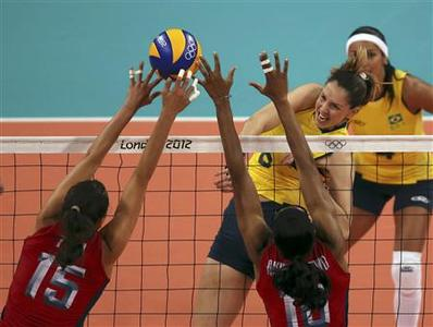 Brazil's Thaisa Menezes spikes the ball as Logan Tom and Foluke Akinradewo of the U.S. try to block the shot and Brazil's Paula Pequeno looks on from behind during their women's Group B volleyball match at the London 2012 Olympic Games at Earls Court July 30, 2012. REUTERS/Ivan Alvarado