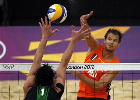 Reinder Nummerdor (R) of the Netherlands spikes the ball against Germany's Jonathan Erdmann during their men's preliminary round beach volleyball match at the London 2012 Olympic Games at Horse Guards Parade July 31, 2012. REUTERS/Lucy Nicholson