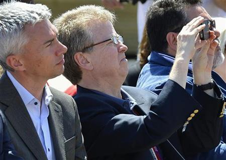 British Olympic Association (BOA) chairman Colin Moynihan (R) takes a photograph as British Olympian Jonathan Edwards looks on at a ceremony in the Olympic Park in Stratford in east London July 23, 2012. REUTERS/Toby Melville