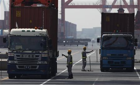 Workers check containers loaded on trucks at a port in Tokyo July 25, 2012. REUTERS/Yuriko Nakao