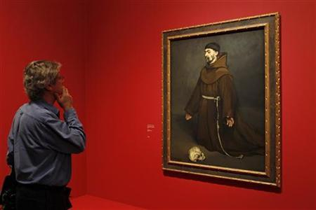 A visitor looks at the painting 'Un moine en priere, 1865' (Monk at Pray) by French painter Edouard Manet (1832-1883) during the media day at the exhibition ''Manet, inventeur du moderne''. REUTERS/Benoit Tessier