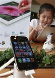 <p>Foto de archivo de una niña jugando con un Ipad ubicado detrás de un Iphone 4S en una tienda de Seúl, ago 24 2012. Google lanzará una nueva versión de su aplicación de video YouTube para el iPhone que permitirá por primera vez contar con anuncios, pero que no tendrá el beneficio de estar precargada en los populares teléfonos inteligentes de Apple. REUTERS/Lee Jae-Won</p>