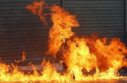 A riot policeman is engulfed by flames after a protester threw petrol bombs in Athens' Syntagma square during a 24-hour labor strike September 26, 2012. Greek police fired teargas at hooded youths hurling petrol bombs and stones as tens of thousands took to the streets in Greece's biggest anti-austerity demonstration in months on Wednesday.   REUTERS-Yannis Behrakis
