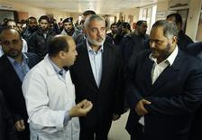 <p>Dans un hôpital de Gaza, visite du chef du gouvernement gazaoui Ismaïl Haniyeh, à des Palestiniens blessés. Israël et les Palestiniens ont fait marche arrière mardi après cinq jours de violences croissantes qui ont amené les deux voisins au bord d'une nouvelle guerre dans la bande de Gaza. /Photo prise le 13 novembre 2012/REUTERS/Ahmed Zakot</p>