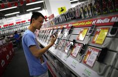 <p>Imagen de archivo de un hombre observando un teléfono móvil en una tienda de artículos electrónicos en el centro de Shanghái, oct 8 2012. La temporada de compras pre-navideñas impulsaría menos de lo usual las ventas de teléfonos móviles básicos este año, a medida que la debilitada economía global obliga a los consumidores a reducir sus adquisiciones, dijo el miércoles la firma de investigación Gartner. REUTERS/Carlos Barria</p>
