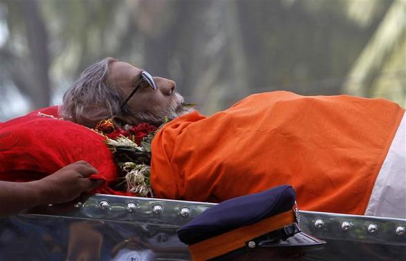 The body of right-wing Hindu nationalist politician Bal Thackeray is carried on a vehicle during his funeral procession in Mumbai, November 18, 2012. Thackeray, one of India's most polarising politicians and leader of an influential right-wing Hindu nationalist party that has dominated politics in the country's richest city for two decades, has died aged 86. Thackeray died of cardio-respiratory arrest on Saturday at his home, one of his doctors, Jalil Parker, said. He had been ill for some time and was rumoured to have died earlier this week. REUTERS/Vivek Prakash