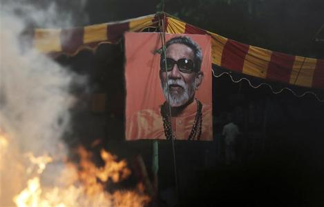A portrait of right-wing Hindu nationalist politician Bal Thackeray is pictured through the heat haze rising from his cremation pyre during his funeral at Shivaji Park in Mumbai, November 18, 2012. REUTERS/Vivek Prakash