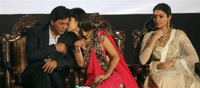 Bollywood actress Katrina Kaif (C) speaks with actor Shah Rukh Khan (L) as actress Anushka Sharma watches during the inauguration ceremony of the 18th Kolkata International Film festival at an indoor stadium in Kolkata November 10, 2012. REUTERS/Rupak De Chowdhuri