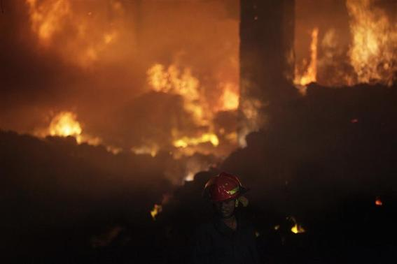 A firefighter tries to control a fire at a garment factory in Savar, outskirts of Dhaka November 24, 2012. REUTERS/Andrew Biraj
