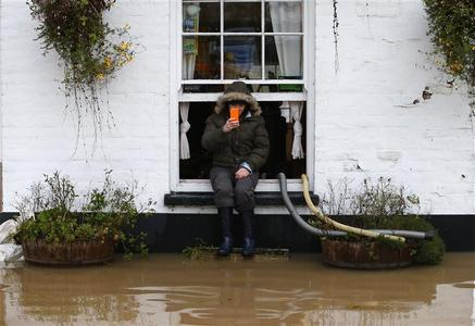 Amy Guy sits on a windowsill of the flooded White Bear pub in Tewkesbury, south western England, November 26, 2012. REUTERS/Andrew Winning