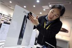<p>Una empleada limpia un anuncio en una concesionaria de Apple antes del lanzamiento del teléfono móvil iPhone 5 en Wuhan, China, dic 13 2012. El debut el viernes del iPhone 5 en China debería darle a Apple Inc algo de aire tras perder recientemente participación en el mayor mercado de telefonía del mundo. REUTERS/Stringer</p>