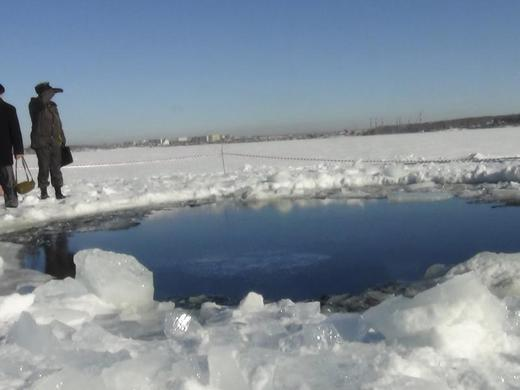 Russian police work near an ice hole said to be the point of impact of a meteor seen earlier in the Urals region, at lake Chebarkul, some 50 miles west of Chelyabinsk, February 15, 2013. REUTERS-Chelyabinsk region Interior Ministry