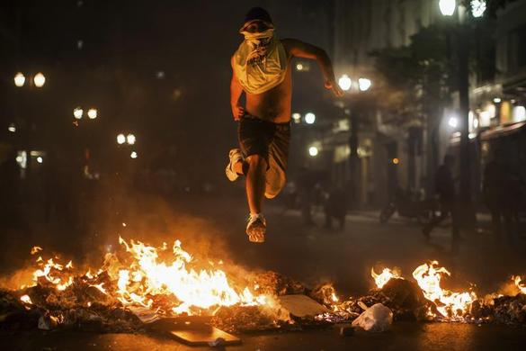A demonstrator jumps over trash set afire during protests against poor public services, police violence and government corruption, in Sao Paulo, June 18, 2013. REUTERS-Victor Moriyama