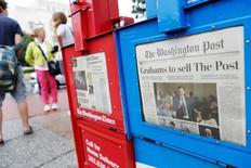 Distributeur de journaux à Washington au lendemain de l'annonce du rachat du quotidien par Jeff Bezos, le patron d'Amazon. Selon une étude du Pew Research Center, une nouvelle vague de financements par des investisseurs issus du secteur des nouvelles technologies est en train de relancer les médias américains, même si le secteur reste confronté à de lourds défis. /Photo prise le 6 août 2013/REUTERS/Jonathan Ernst