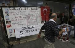 Panneau expliquant des moyens alternatifs d'accéder à Twitter près d'un local de campagne d'un membre de l'opposition à Istanbul. Un tribunal administratif turc a approuvé mercredi un appel visant à mettre fin au blocage de Twitter par les autorités, selon la presse turque, mais on ignore si cette décision va entraîner la reprise immédiate du site de microblogging. /Photo prise le 25 mars 2014/REUTERS/Murad Sezer