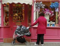 Devant une vitrine à Londres.  Les ventes au détail ont augmenté plus fortement que prévu en février en Grande-Bretagne, grâce aux magasins d'alimentation, selon les données de l'Office national de la statistique qui montrent que la consommation des ménages reste un moteur de croissance. Les ventes ont augmenté de 1,7% en volume sur un mois.  /Photo prise le 25 mars 2014/REUTERS/Luke MacGregor