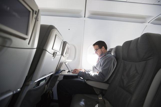 A man uses his laptop to test a new high speed inflight Internet service named Fli-Fi while on a special JetBlue media flight out of John F. Kennedy International Airport in New York December 11, 2013. REUTERS/Lucas Jackson/Files
