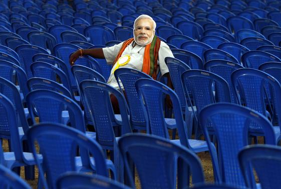 A supporter of Hindu nationalist Narendra Modi, prime ministerial candidate for India's main opposition Bharatiya Janata Party (BJP), wears a mask depicting Modi as he sits before the start of an election campaign rally in Chennai April 13, 2014. REUTERS/Babu